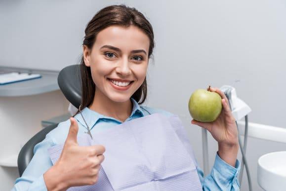 Junge Frau mit Apfel beim Zahnarzt
